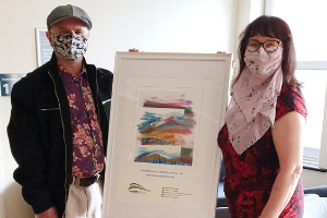 Local artist Oliver Street handing over his artwork Expressions of Exmoor to council Chairman Julie Hunt Artwork handed over to thank council for community service